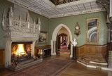 View of the Main Hall at Tyntesfield with huge stone carved fireplace and a pointed arched doorway to the Ante Room and Drawing Room beyond