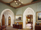 The Entrance Hall at Tyntesfield showing large carved stone arches to Oak Room lobby & Ante Room, flower patterned carpets, large chest & china cabinet