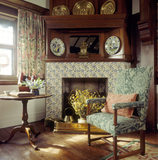 Oak Room at Wightwick, still life of chair with Morris fabric by the fireplace, light streaming in through window onto table with arrangement of flowers