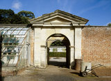 The arched gateway from the old walled garden at Tyntesfield, showing part of a greenhouse, a galvanised water trolley and a view of a plinth of an old sundial through the archway