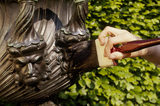 A detail of wet brushing a bronze urn at Anglesey Abbey