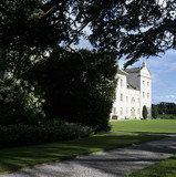 A view of the west front of Saltram slightly hidden by hedge