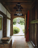 Axial view along the Screens Passage from back to front, at Stoneacre, a Wealden house in Kent, with doors open showing stone path to open wrought-iron gate