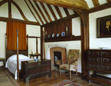 View towards fourposter bed and fireplace in the Solar at Stoneacre, Kent, showing beamed ceiling and wooden archway