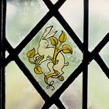 Stained glass panel of a rabbit in a window on the staircase at Stoneacre