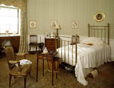 The brass bed in the Oval Bedroom holding a large feather fan There are various items of furniture including a table from the Digby collection