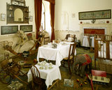 A view of the Nursery with many toys strewn around and a table set for breakfast and a dolls tea party