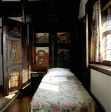 The bed in the Oak Room at Wightwick Manor, with light falling on the counterpane