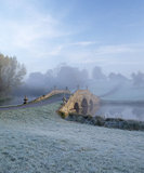 Oxford Bridge at Stowe Landscape Gardens in early morning with frost on the grass and a pale blue sky