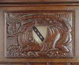 A close-up detail of the wood carving on a panel in the Great Hall at Ightham Mote of a dragon with coat of arms in the middle