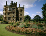 View across the circular Rose Garden to the east front of Gawthorpe Hall, originally built in 1600-1605, and rebuilt in 1851