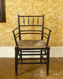 "Rush-seated, ebonised ""Sussex"" chair designed by Ford Maddox Brown in the Upstairs Corridor at Standen, West Sussex"