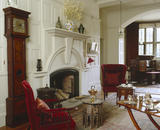 The Hall at Standen, West Sussex, showing the chimney-piece designed by Webb and an early eighteenth-century English marquetry long-case clock made by Cornelius Herbert