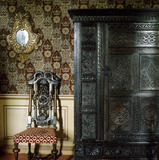 An intricately carved cabinet and chair in the King Charles Room at Dunster Castle