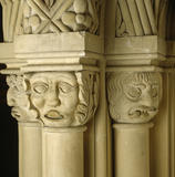 Close-up of a group of three carved limestone capitals between the windows of top landing at Penrhyn Castle