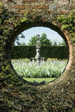 A `porthole' in a high brick wall showing a figure on a stone pedestal set in a bed of bearded irises