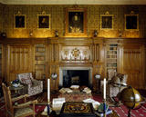 View of The Library at Charlecote Park including; the fireplace, book shelves, five paintings, chairs, candlesticks, a globe, a table and books