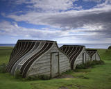 Close-up view of up-turned boats which have been converted into huts at Lindisfarne Castle