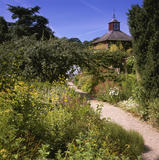 The herb garden with a backdrop of the clock tower and weathervane, at Acorn Gardens