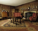 View of the Great Parlour at Lytes Cary Manor, showing the fireplace, early C17th panelling, internal porch, early C18th walnut chest of drawers, chair and red damask high back walnut settee typical of 1690's