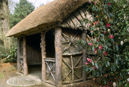 Close view of the rustic thatched summer house at Trelissick, Cornwall