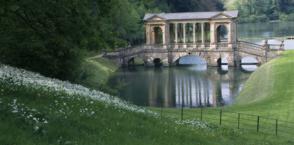 View of the Palladian Bridge at Prior Park built over the first of three dams with woods behind and a slope with wild garlic in the foreground