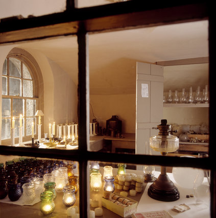 Looking through a window into the Lamp room at Penrhyn Castle showing candlesticks in front of an arched window