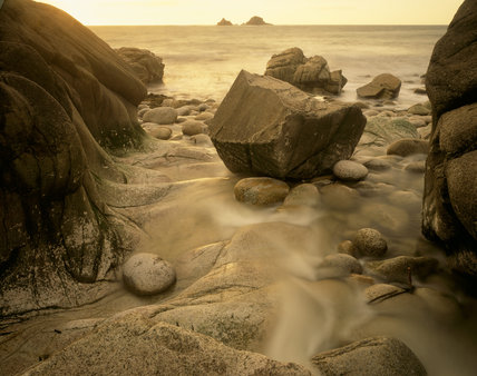 A rock nestled in a crag on the beach at Cape Cornwall with the tide running past, out to the sea