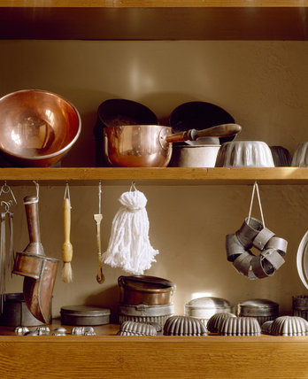 A close up view of kitchen utensils at Penrhyn Castle in a cupboard in the Pastry Room in the domestic quarters, including bowls, brushes, cake tins and moulds