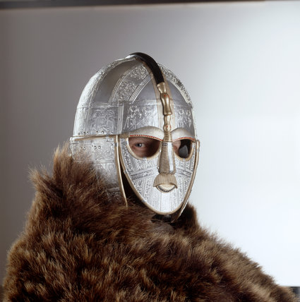 Replicas of finds from the Sutton Hoo Saxon burial site - richly decorated Anglo-Saxon helmet of war modelled by man wearing a bear skin