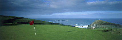 The golf course at Cape Cornwall, with a dark brooding sky and the red flag flapping in the wind