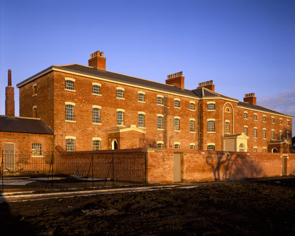 An oblique view of the Front Facade of this Workhouse,showing the wall of the Exercise Yard, taken from the West at Sunset