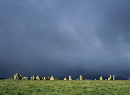 Castlerigg Stone Circle silhouetted against a stormy sky