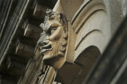 A close up detail of a profile of a face carved in the stonework on the Pavilion in the garden at Cliveden