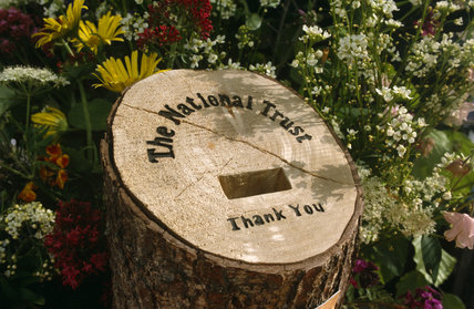 National Trust collection box hewn from a tree trunk and set in a flower bed in the walled garden at Llanerchaeron near Aberaeron