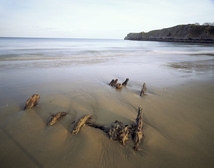Wreckage on the shore of Barafundle Bay, with Stackpole Head in the distance
