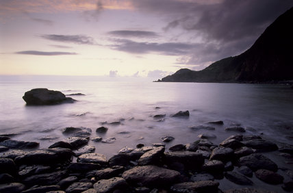 View of Woody Bay, North Devon with rocks in the foreground at dawn