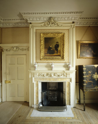Room view of the Morning Room at Peckover showing the 18th century carved and marble fireplace, with a painting hanging above it