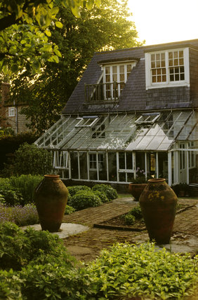 A view of the South Front from the garden showing the conservatory added in the 1940's and two large stone urns