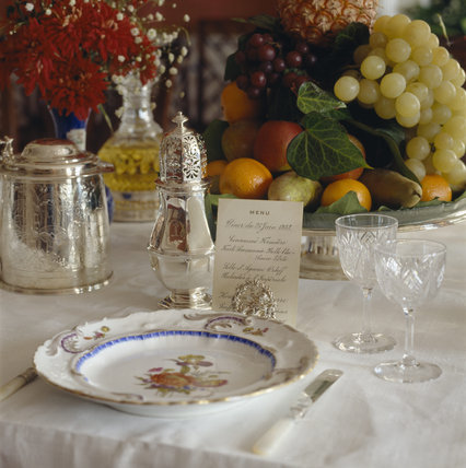 A close-up of a place setting in the dining table in the Dining Room showing silverware, cutlery, menu cards, wine glasses and plate