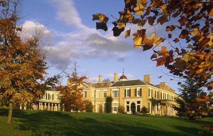 The west face of Polesden Lacey, catching the afternoon sun, with trees in bronze autumn colour in the foreground