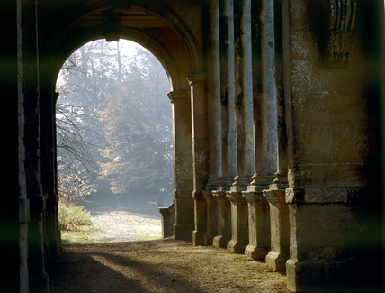 The C18th Palladian Bridge at Stowe Landscape Gardens with light coming through the arch and trees in the background