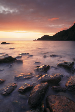 View of Woody Bay, North Devon with rocks in the foreground at sunset