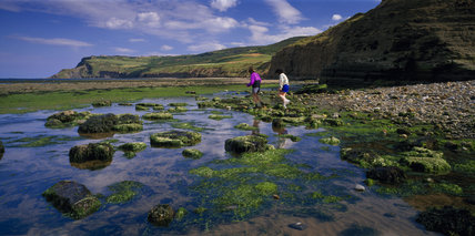 A view along the beach at Boggle Hole with people walking on rocks covered with seaweed