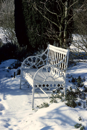 A white ornamental bench seat lit by weak sunlight sits amongst the snow
