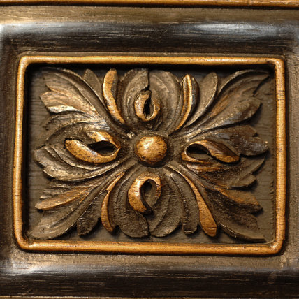 Detail of part of a carved wooden cabinet stand in the Grey Room at Snowshill Manor, home of the collector Charles Wade