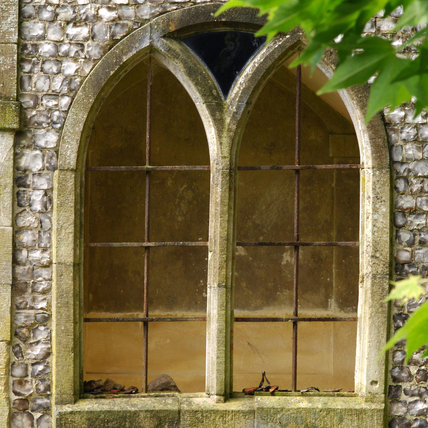 A double arched window with stone mullions, set into a flint wall at Mottisfont Abbey