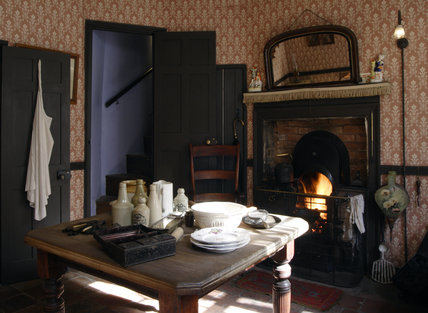 The front parlour of the 1870s house at the Birmingham Back to Backs, with a lit fire, an overmantle mirror and table laid with crockery