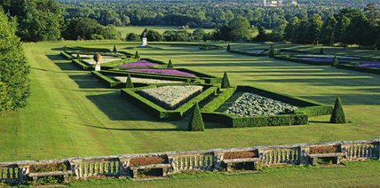 Long view of Parterre from terrace at Cliveden, Grade 1 listed garden, formal style garden with triangular shaped flower beds, edged with trimmed hedges & bushes