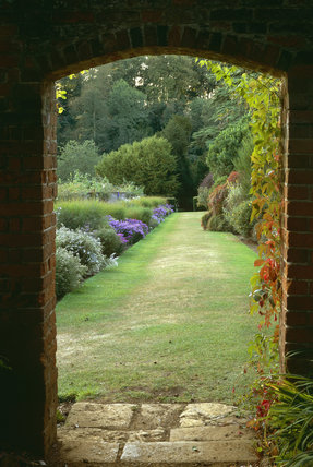 The Dry Banks in the garden viewed through an archway, at Upton House, Warks